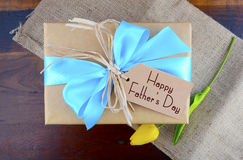 Happy Fathers Day Natural Kraft Paper Gift. Happy Fathers Day natural kraft paper wrapped gift owith pale blue ribbon on dark wood background royalty free stock images