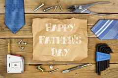 Happy Fathers Day on paper with frame on wood. Happy Fathers Day message on rustic paper with frame of tools and ties on a wooden background royalty free stock photos