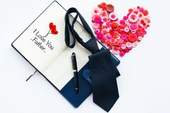 Happy fathers day, red button in heart shape and dark tie on book and luxury pen with text I Love you father stock image
