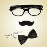 Happy fathers day. Sentence happy fathers day and glasses, mustache and bow tie forming a man face in a beige background, with a retro effect stock images