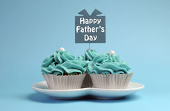 Happy Fathers Day special treat blue and white beautiful decorated cupcakes. With message on blue background royalty free stock photo