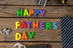 Happy fathers day text by neckties and work tools on table. Overhead view of happy fathers day text by neckties and work tools on wooden table royalty free stock images
