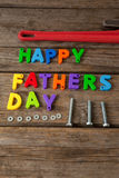 Happy fathers day text with pipe wrench and bolts on table Stock Image