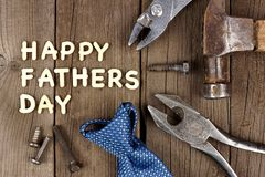 Happy Fathers Day wood letter greeting with tools and tie Royalty Free Stock Images