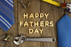 Happy Fathers Day on wood with tools and ties. Happy Fathers Day wooden letters on a rustic wood background with tools and ties frame stock photos