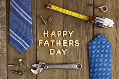 Happy Fathers Day on wood with tools and ties. Happy Fathers Day wooden letters on a rustic wood background with tools and ties frame royalty free stock photo