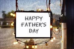 Happy Fathers Day written on hanging sign surrounded by party lights in shop window with semi-transparent dark solar shades behind. A Happy Fathers Day written stock image