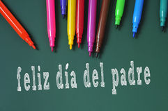 Happy fathers day written in spanish. Feliz dia del padre, happy fathers day written in spanish in a chalkboard, and some felt-tip pens of different colors stock images