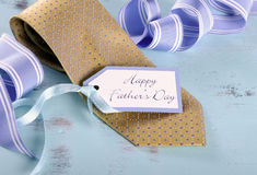 Happy Fathers Day yellow tie with gift tag. On vintage aqua blue rustic shabby chic table stock photography