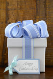 Happy Fathers Gift with blue and white gift on wood background. Royalty Free Stock Images