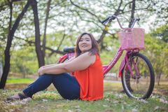 Happy fatty woman posing with bicycle Stock Photo