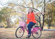 Happy fatty woman posing with bicycle Royalty Free Stock Photo