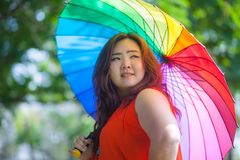 Happy fatty woman with umbrella. Happy fatty asian woman with umbrella outdoor in a park Royalty Free Stock Photos