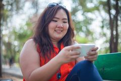 Happy fatty woman using mobile phone. Happy fatty asian woman using mobile phone outdoor in a park Royalty Free Stock Image
