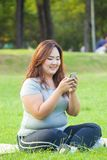 Happy fatty woman using mobile phone Royalty Free Stock Images