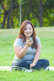 Happy fatty woman using mobile phone. Happy fatty asian woman using mobile phone outdoor in a park Royalty Free Stock Images