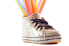 Happy feet. Ceramic shoe with colorfull straws, white background Stock Photography