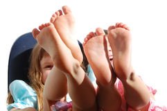 Happy feet. Four small feet of two little girls having fun Royalty Free Stock Photo