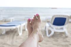 Happy Feet on the Beach. Feet on beach chair in the summer Stock Photos