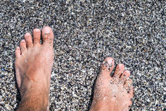 Happy feet. Feet on the beach with wet sand in summer time Royalty Free Stock Image