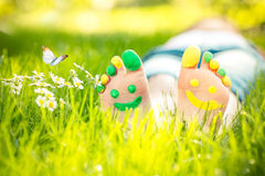 Happy feet. Child lying on green grass. Kid having fun outdoors in spring park Royalty Free Stock Image