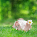 Happy feet with daisy flower outdoors. Kid having fun in spring park. Child lying on green grass. Ecology concept Stock Photography