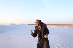 Happy fellow Arabian, walks through desert, smiles and enjoys li Royalty Free Stock Photos