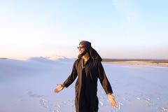 Happy fellow Arabian, walks through desert, smiles and enjoys li Royalty Free Stock Photo