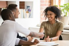 Happy female african vacancy candidate shaking hand of hr manager. Happy female african vacancy candidate shaking hand of hr recruiting manager congratulating stock photos