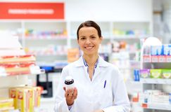 Happy female apothecary with drug at pharmacy. Medicine, pharmaceutics, healthcare and people concept - happy female apothecary with drug at pharmacy stock photos