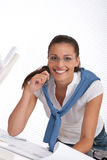 Happy female architect with plans at the office Royalty Free Stock Photos