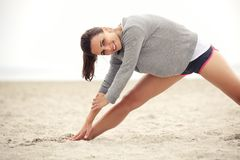 Happy Female Athlete Exercising on the Beach. Outdoor female athlete doing her morning stretching and yoga exercise on the beach while smiling and looking happy Stock Image