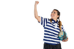 Happy female athlete holding rugby ball while standing with clenching fist Royalty Free Stock Photos
