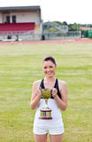 Happy female athlete holding a trophy Stock Images