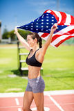 Happy female athlete holding up american flag on running track Stock Photo