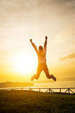 Happy female athlete jumping towards the sun Stock Images