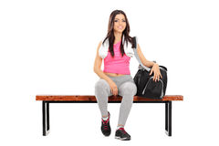 Happy female athlete sitting on a wooden bench Royalty Free Stock Images