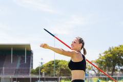 Happy female athlete about to throw a javelin. In the stadium stock image