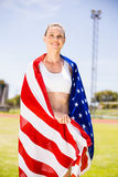 Happy female athlete wrapped in american flag. In stadium Stock Images