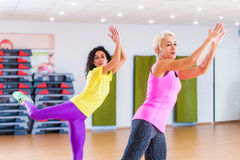 Happy female athletes doing aerobics exercises or Zumba dance workout to lose weight during group classes in fitness. Center royalty free stock image