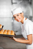 Happy Female Baker With Fresh Breads In Baking Tray Royalty Free Stock Images
