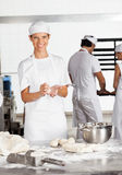 Happy Female Baker Making Dough Balls In Bakery Royalty Free Stock Photography