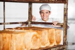 Happy Female Baker Pushing Bread Rack Royalty Free Stock Images