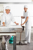Happy Female Baker's In Uniform Cleaning Bakery Stock Photography