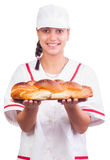 Happy female baker in white uniform and cap Stock Photography