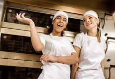 Happy female bakers chatting. At baking manufacture stock image