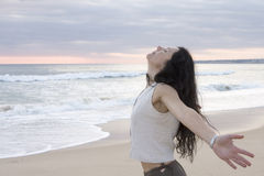 Happy female at beach throwing her arms back. Behind her Royalty Free Stock Photo