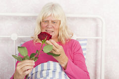 Happy female in bed with rose Stock Images