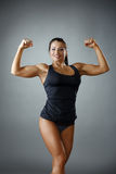 Happy female bodybuilder showing her biceps. At camera Royalty Free Stock Photo