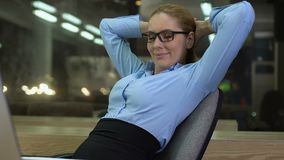 Happy female boss relaxing on office chair, satisfied with project results, work stock video